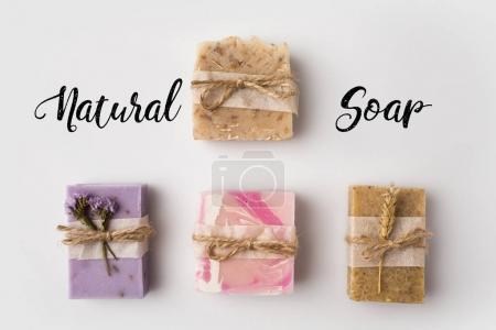 Photo pour Vue de dessus de différents savon artisanal avec lettrage savon naturel sur surface blanche - image libre de droit