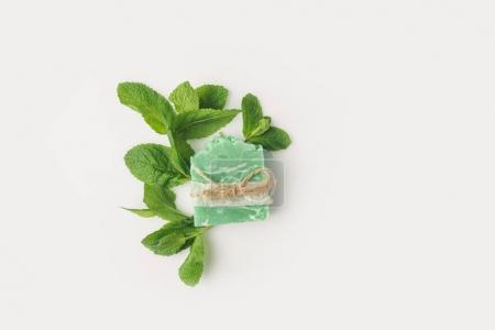 Photo pour Vue de dessus du savon à la menthe artisanal avec feuilles sur surface blanche - image libre de droit
