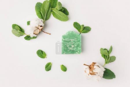 Photo pour Vue du dessus du savon à la menthe fait maison avec des feuilles et des fleurs de coton sur surface blanche - image libre de droit