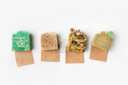 Photo pour Vue de dessus du savon artisanal divers sur papiers kraft sur surface blanche - image libre de droit