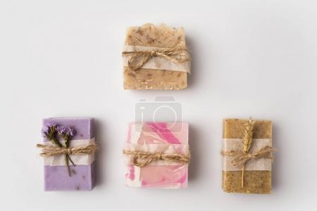 Photo for Top view of different decorated homemade soap on white surface - Royalty Free Image