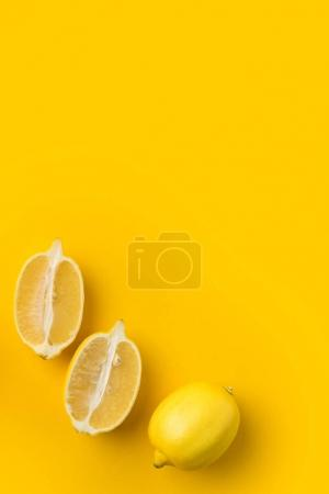 Photo for Two halves of lemon and single lemon isolated on yellow - Royalty Free Image