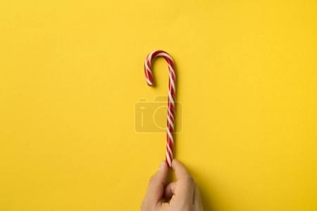 Photo for Cropped image of man holding candy stick isolated on yellow - Royalty Free Image