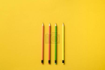 Four colored pencils with erasers