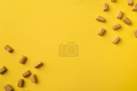 Photo for Scattered sweet iris milk candies isolated on yellow - Royalty Free Image
