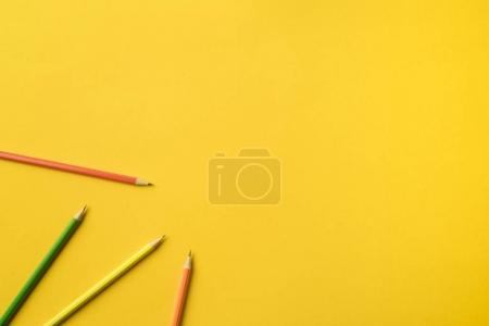 Photo for Top view of Four colored pencils isolated on yellow - Royalty Free Image
