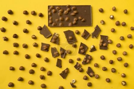 Photo pour Vue de dessus de la barre de chocolat avec des morceaux éparpillés et écrous isolés jaune - image libre de droit