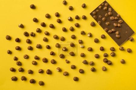 Photo pour Vue de dessus de la barre de chocolat avec noix épars isolé jaune - image libre de droit