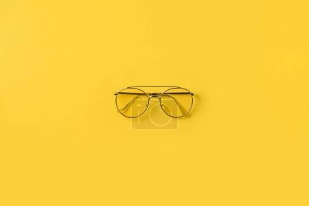 Photo for Top view of one stylish Glasses isolated on yellow - Royalty Free Image