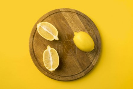 Photo for Top view of lemons on a wooden board isolated on yellow - Royalty Free Image