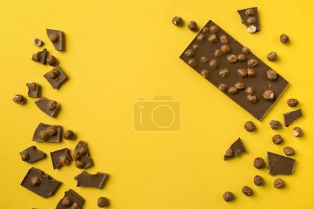 Photo for Milk Chocolate bar with scattered pieces and nuts isolated on yellow - Royalty Free Image