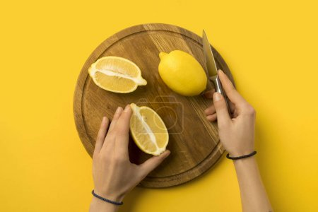 Photo for Cropped image of woman cutting lemons on wooden board isolated on yellow - Royalty Free Image