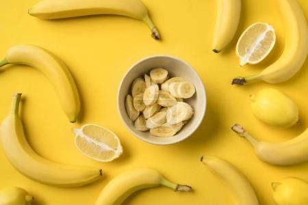 Foto de Vista superior de la placa con corte mitades plátanos y limones aislado sobre fondo amarillo - Imagen libre de derechos
