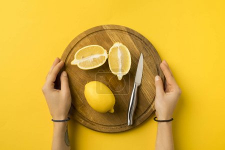 Photo for Cropped image of woman holding wooden board with lemons isolated on yellow - Royalty Free Image