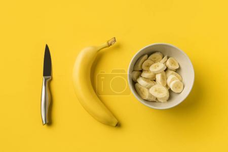 Plate with cut bananas and knife
