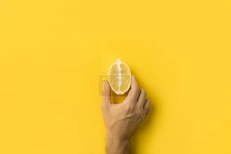 man holding half of lemon