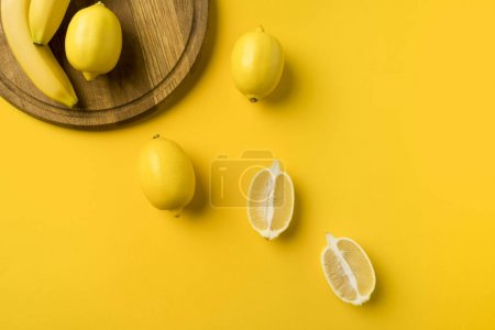 Photo for Top view of lemons and bananas with wooden board isolated on yellow - Royalty Free Image