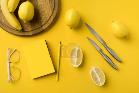 lemons with knifes and notebook with pencil