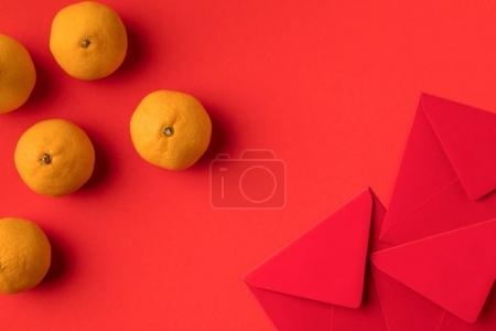 Photo for Top view of decorative festive red envelopes and tangerines isolated on red - Royalty Free Image