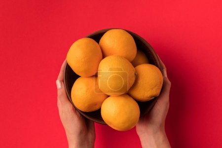 hands holding bowl with tangerines
