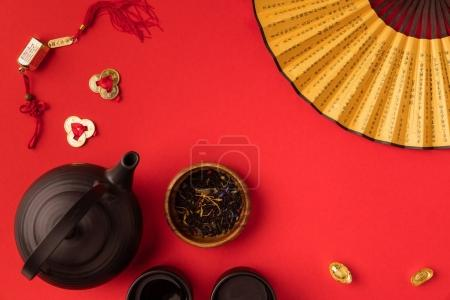 Photo for Top view of oriental tea set, decorations and fan with characters isolated on red - Royalty Free Image