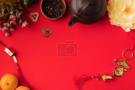 Photo pour Vue de dessus de décorations orientales, de mandarines, de fleurs et de thé ensemble isolé sur rouge - image libre de droit