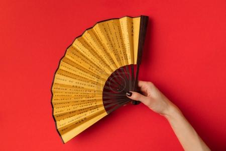 Photo for Cropped shot of female hand holding decorative oriental fan isolated on red - Royalty Free Image
