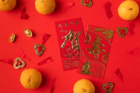 Foto de Vista superior de China tarjeta de felicitación con caligrafía, decoraciones orientales y mandarinas aislados en rojo - Imagen libre de derechos