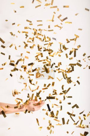 Photo for Cropped image of woman catching falling golden shiny confetti on white - Royalty Free Image