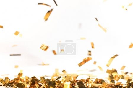 Photo for Falling pieces of golden confetti on white - Royalty Free Image