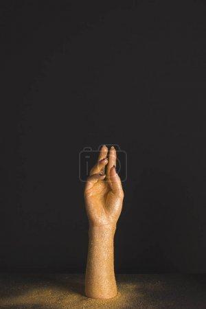 Photo pour Main de cire en or paillettes brillantes sur fond noir - image libre de droit