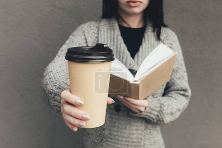 Photo for Cropped view of woman in sweater reading book and holding coffee to go - Royalty Free Image