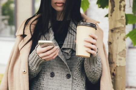 Photo for Cropped view of woman in coat holding smartphone and coffee to go - Royalty Free Image