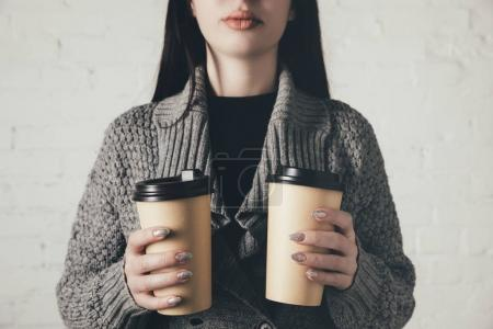 Photo for Cropped view of woman in sweater holding two disposable cups - Royalty Free Image