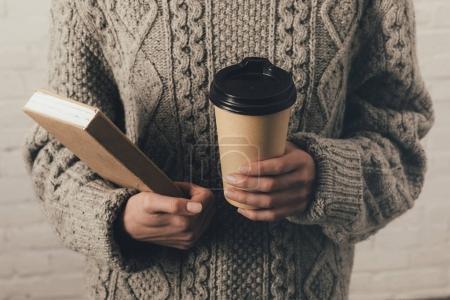 Photo pour Vue recadrée de femme en pull tenant livre et café pour aller - image libre de droit