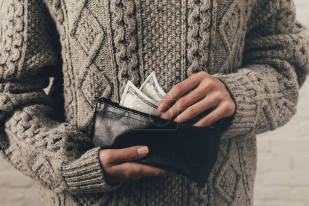 woman holding wallet with dollar banknotes