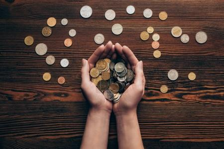 Photo for Cropped view of female hands with coins on wooden tabletop - Royalty Free Image