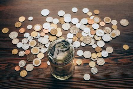 Photo for Glass jar with banknotes on wooden tabletop with coins - Royalty Free Image