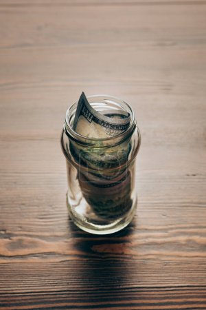 glass jar with dollar banknotes