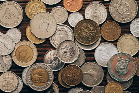 Photo for Top view of collection of coins on wooden tabletop - Royalty Free Image