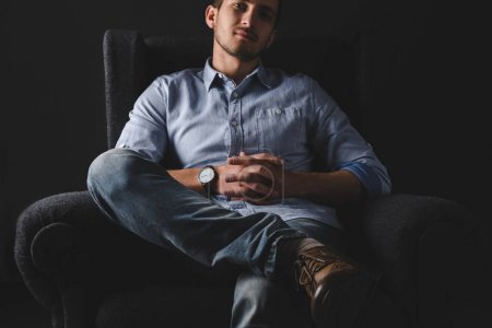 Photo for Man in shirt sitting and relaxing in armchair - Royalty Free Image