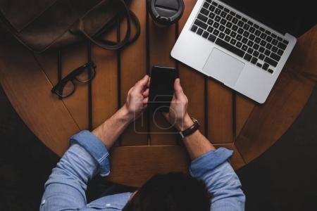 Photo for Overhead view of freelancer using smartphone at wooden table with laptop, leather bag and coffee to go - Royalty Free Image