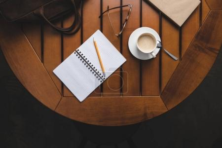 Photo for Top view of opened notepad with pencil and coffee on wooden table - Royalty Free Image