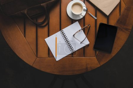 Photo for Top view of opened notepad and cup of coffee and digital tablet on wooden table - Royalty Free Image