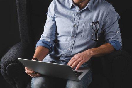 Photo pour Vue recadrée de l'homme à l'aide d'un ordinateur portable assis dans un fauteuil - image libre de droit
