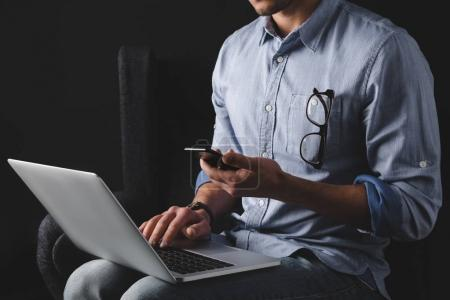 Photo for Cropped view of man working with smartphone and laptop while sitting in armchair - Royalty Free Image