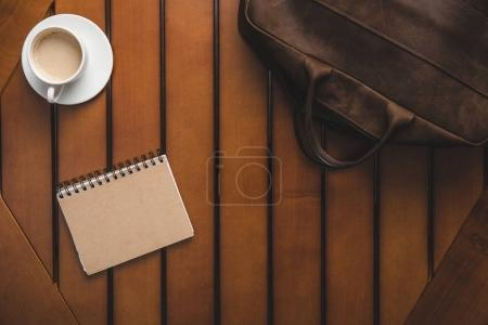 leather bag, notepad and coffee