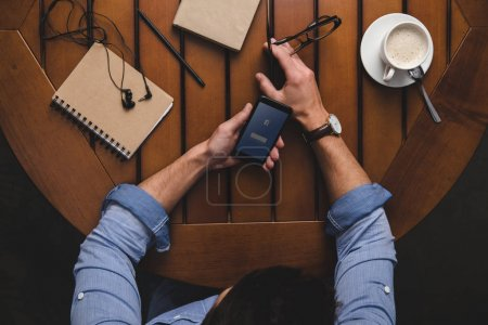 Photo for Overhead view of man using smartphone with facebook website while sitting at table with coffee and notepads - Royalty Free Image