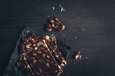 Photo for Top view of dark chocolate with nuts pieces on crumpled paper on table - Royalty Free Image