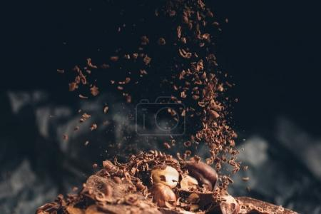 Photo for Shredded chocolate pieces falling on a chocolate pile with nuts - Royalty Free Image